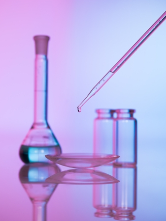 probe: pipette dropping a transparent liquid in a dish with two empty glass recipients and a erlenmeyer flask with blue transparent liquid in the background against a gradient purple background Stock Photo