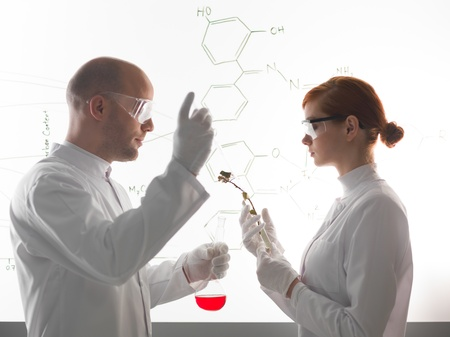 eye protection: Two young scientists wearing medical protection uniform while making a chemical experment