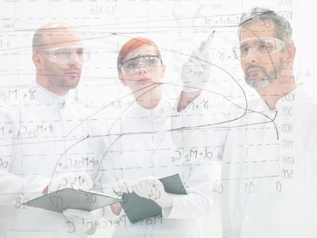 technologists: Three scientists standing discussing a diagram and analysing results of an experiment on a glass interface, they are behind it facing the camera