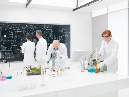 Team of scientists in a laboratory working on chemical testing, microscopy and discussing and analysing complicated molecular formulae on a large blackboard