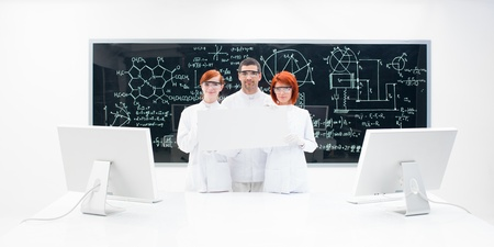 Three lab technicians dressed in white with two monitors against a blackboard with formulas and diagrams on it. photo