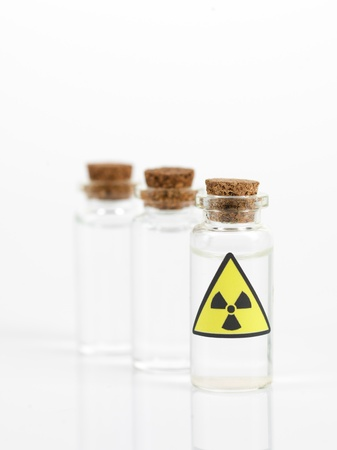 radioactive: white background with three small glass transparent bottles with a brown cork and a radioactivity warning label