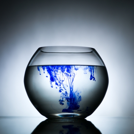 blending: spherical bowl filled with a transparent solution which is blending with a blue dye against a gradient grey background and laying on a reflective surface