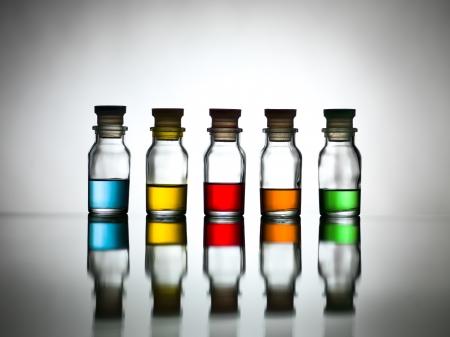 pocion: Cinco botellas con diversos colores de contenidos reflejados en una tabla