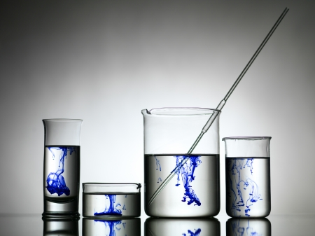 dripped: Gradient grely background with four different sizes glasses filled with colourless solution and blue dye dripped in them Stock Photo