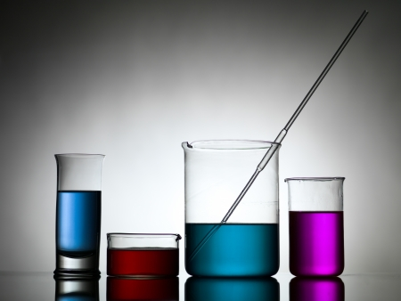 blending: different sizes beakers filled with colored liquid whith a dropper in one, against a gradient gray background and laying on a reflective surface Stock Photo