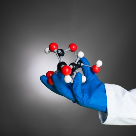 didactic: hand in blue rubber glove and white lab coat holding a 3d model of a mollecular structure made of white, black and red spheres with grey bonds, against a gradient grey background Stock Photo