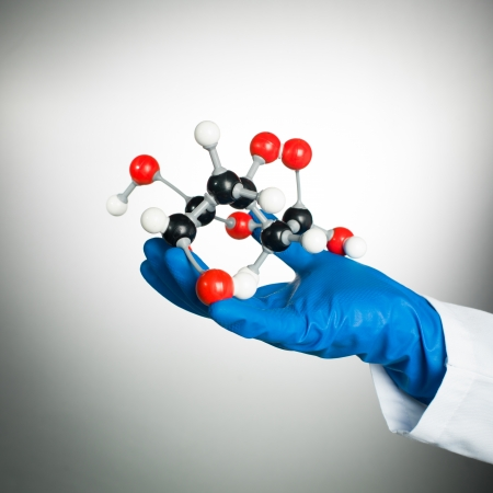hand in blue rubber glove and white lab coat holding a 3d model of a mollecular structure made of white, black and red spheres with grey bonds, against a gradient white to grey background photo