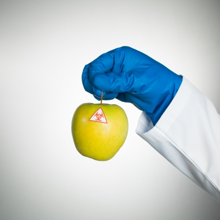 constituent: white background with a bio hazardous yellow ripe apple held by a hand in a blue rubber glove and in a lab coat