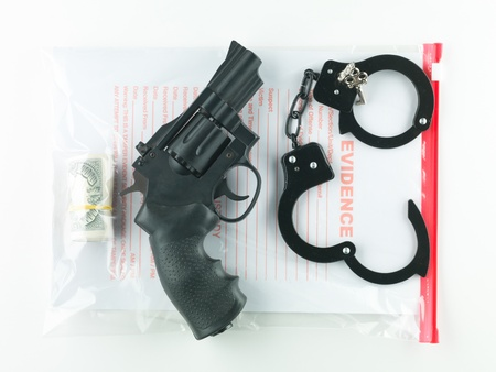criminal investigation: aerial view of a bag marked evidence containing a roll of money, a revolver and a pair of handcuffs with their keys, on a white background
