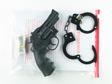 delincuencia: vista aérea de una bolsa marcada evidencia que contiene un rollo de dinero, un revólver y un par de esposas con sus llaves, sobre un fondo blanco