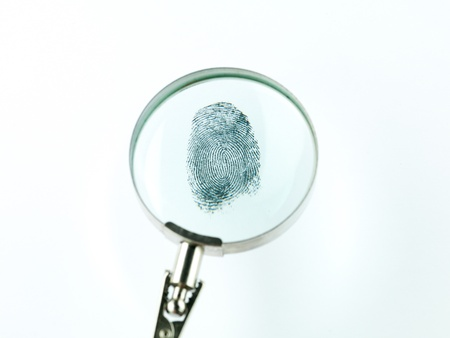 incriminate: top view of a fingerprint viewed through a magnifying glass, against a white background Stock Photo
