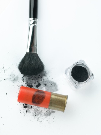 shotgun bullet cartounche with a fingerprint revealed by a brush and printing dust next to a small dust container and a brush, against a white background photo