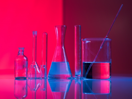basis: Red background with experimental glass containers and their reflection on a table in a blue light