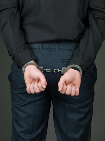 apprehend: back view of a person dressed in black, hancuffed with their hands behind their back and their palms closed Stock Photo