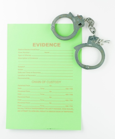 aerial view of a green unfilled form with the title evidence and a pair of handcuffs, with keys, against a white background photo
