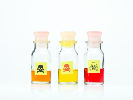 frontal view of three transparent colorless bottles filled with orange, yellow and red liquid and marked as poisonous on a white background Stock Photo - 20701008