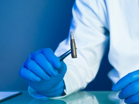 person in a white lab coat and blue rubber gloves, holding a bullet with a tweezers on a reflective surface