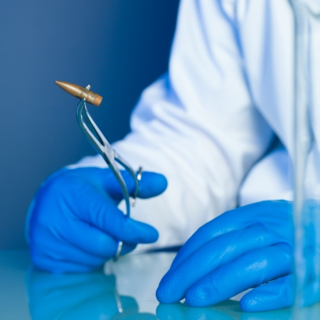didactic: person in a white lab coat and blue rubber gloves, holding a bullet on a reflective surface