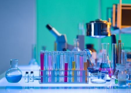 close-up of medical tools and glassware filled with colorful liquids placed on a table in a laboratory