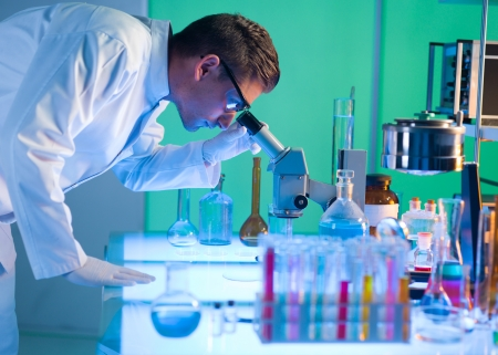 side view of male scientist analysing something through a microscope in a laboratory photo