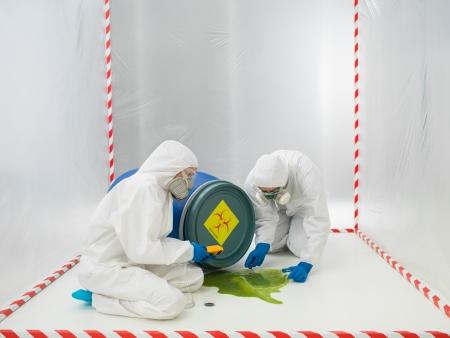 sustancias toxicas: Dos técnicos de laboratorio o científicos de cheques un riesgo biológico que se ha derramado desde un tambor volcado en una tienda de contención