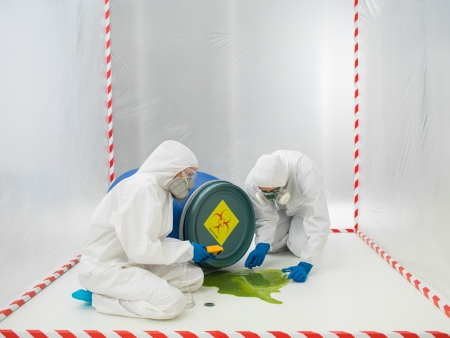 overturned: Two laboratory technicians or scientists checking a biohazard that has spilled from an overturned drum in a containment tent