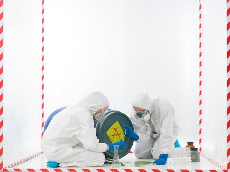 riesgo biologico: especialistas en la recogida de muestras de un accidente de riesgo biológico, en un cubo rodeado con una cinta roja y blanca