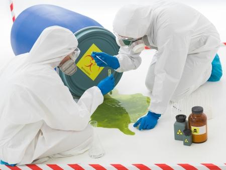 especialistas: primer plano de dos especialistas en la recogida de muestras de un charco de l�quido de desecho t�xico con trajes de protecci�n y m�scaras