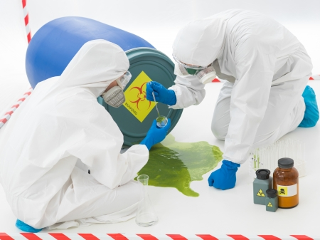 hazard tape: close-up of two specialists collecting samples from a puddle of toxic waste liquid wearing protection suits and masks