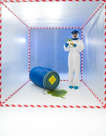 female specialist standing in a cube surrounded with red and white tape, with a blue barrel near her labeled as biohazard photo