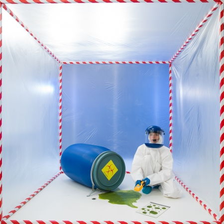 female specialist measuring the level of contamination from a puddle of toxic waste spilling from a biohazard barrel, in a white cube surounded by red and white tape photo