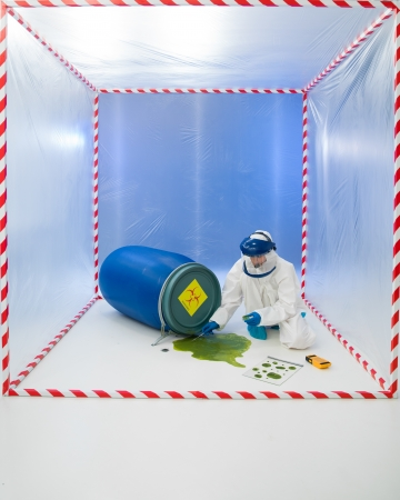 containment: Woman in a biohazard suit testing a spillage of green liquid from a drum inside a containment tent