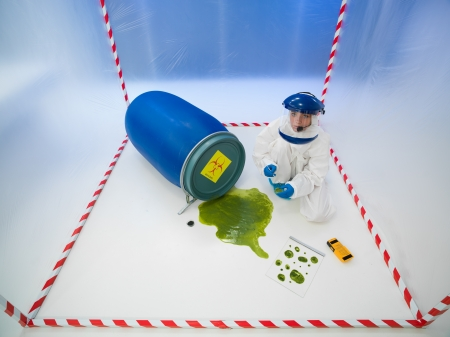 upper view of female specialist collecting samples from a green puddle of toxic waste, in a chamber surrounded by red and white tape Stock Photo - 20691437