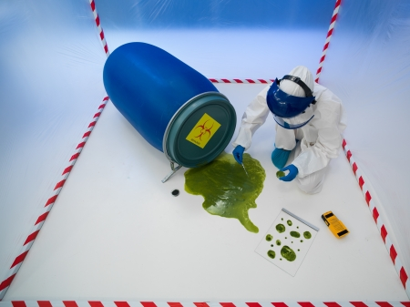 hazardous waste: upper view of specialist collecting samples from a green puddle of toxic waste, in a chamber surrounded by red and white tape Stock Photo