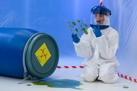 hazardous waste: close-up of female scientist wearing white suit and protective mask, analysing samples collected from a biohazard accident