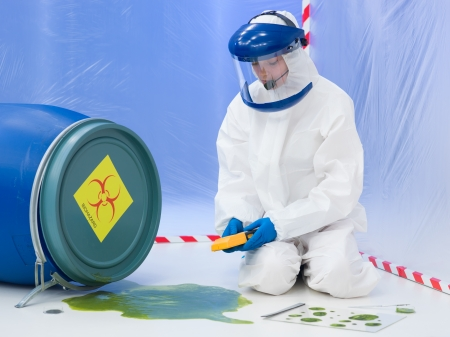 hazardous waste: close-up of female scientist wearing white protection suit and mask, measuring the level of contamination at  a biohazard accident