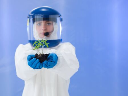 close-up of female biologist wearing white protection suit and blue mask holding plant seedling in her hands photo