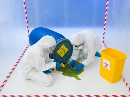hazardous waste: Two scientists in full protective biohazard suits attending to a biohazard chemical spill of green liquid from an overturned drum taking samples and performing tests in a containment tent