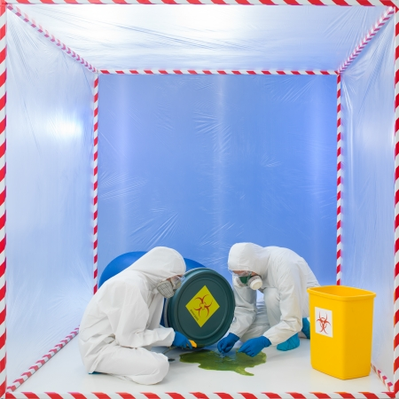 quarantine: specialists wearind white protection suits and gas masks collecting samples from a liquid spilling from a blue biohazard barrel Stock Photo