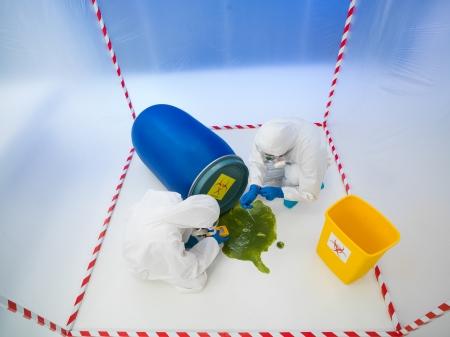 riesgo biologico: Vista superior de dos especialistas wearind trajes de protección blancos y máscaras de gas recolección de muestras de un líquido se derrame de un barril azul, en un cubo rodeado de rojo y cinta blanca
