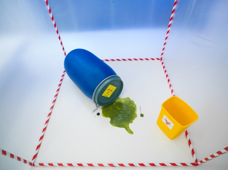 upper view of toxic waste spilling from a blue barrel in a white cube surrounded with red and white tape, with a yellow bin inside it photo