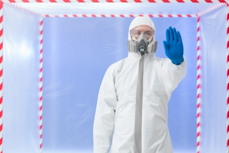 quarantine: close-up of male scientist standing wearing white protection suit, glasses and gas mask, with stop gesture, in a transparent cube surrounded with red and white tape