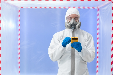 close-up of male specialist wearing white protection suit, rubber gloves and gas mask, holding a measuring device in his hands, in a chamber surrounded wwith red and white tape photo