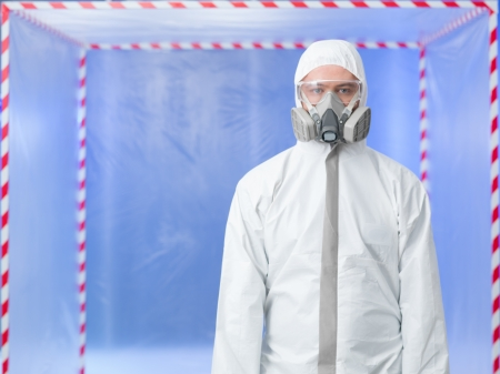 quarantine: male researcher wearing protection equipment, standing in a chamber surounded with red and white tape