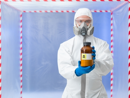 quarantine: close-up of man wearing protection equipment holding a bottle labeled as deadly substance, in a chamber surounde with red and white tape Stock Photo