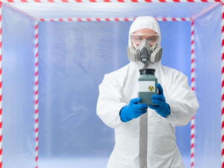 male scientist wearing protection equipment holding a toxic waste container, inside a chamber surounded with red and white tape photo