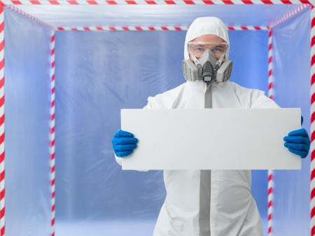 quarantine: male scientist wearind protection equipment holding an empty ad banner, in a chamber surounded with red and white tape