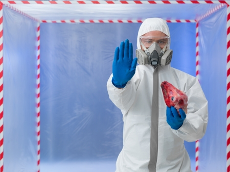 head protection: close-up of man wearing protection suit, gloves and gas mask, holding a dead lambs head, with stop gesture, in a chamber surounded with red and white tape Stock Photo