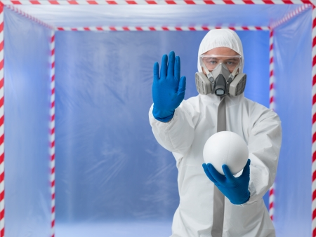 protective suit: person dressed in a bio hazard protective suit making a halt gesture with one hand and holding a styrofoam sphere in the other in front of a confinement tent